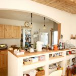 アール垂れ壁のあるオープンキッチンとオリジナル食器棚